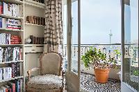 elegant armchair beside the bookshelves, and balcony with potted plants offer amazing view of Paris