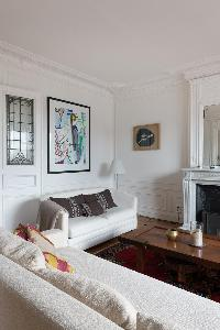 cozy living room with sets of white sofas facing beneath frameda rtwork in Paris luxury apartment