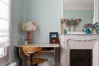 pretty third bedroom with powder blue walls and colourful butterfly artwork in Paris luxury apartmen