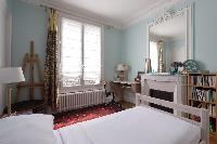 pretty third bedroom with powder blue walls and ornamental fireplace beneath ornate mirror  in Paris