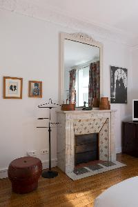 marble-tiled ornamental fireplace beneath ornate mirror, and antique pieces in Paris luxury apartmen