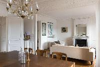 ornate ceiling, elegant chandelier sits on top of a wooden dining table and cream sofas on the other
