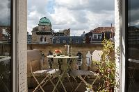 balcony with small round table for 2 overlooking Parisian neighborhood