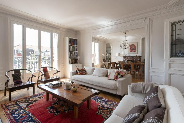 cozy living room with period wainscoting and corniced ceiling in Paris luxury apartment