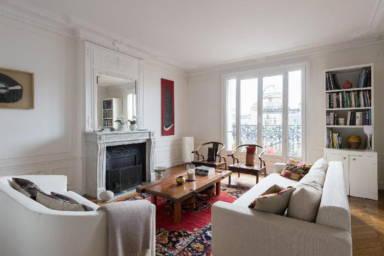 3-bedroom Paris luxury apartment smartly furnished with herringbone floor, gray sofas, honeyed wood