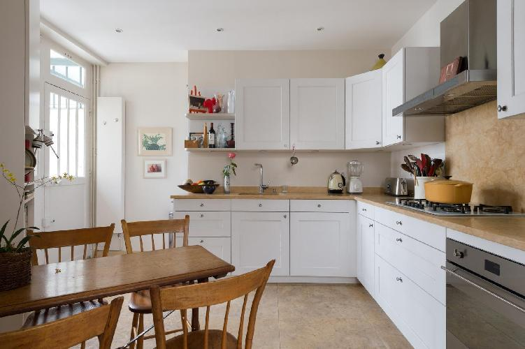 well-equipped kitchen with wooden dining table for 4 in Paris luxury apartment