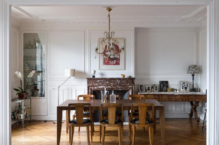 classic dining area with elegant chandelier, long wooden table for 6, and ornamental fireplace in Pa