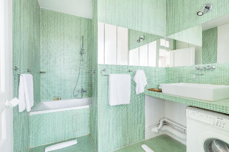 mint green-tiled bath with integrated shower in Paris luxury apartment