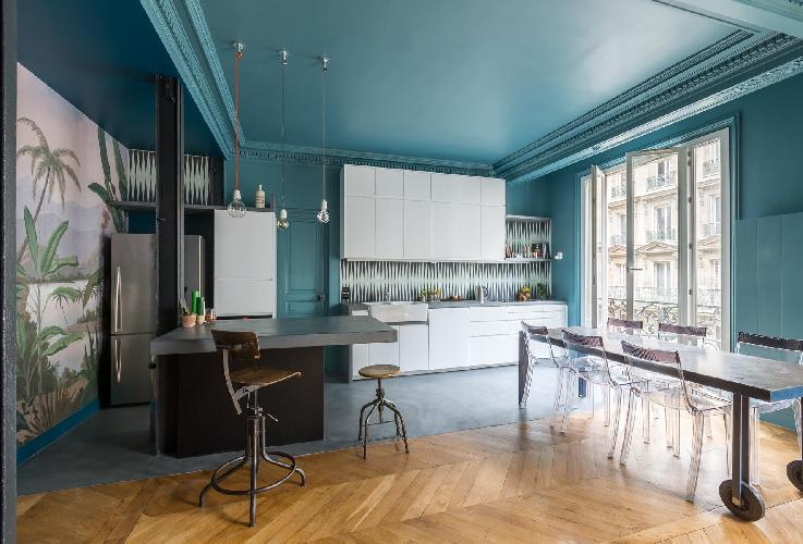 teal-walled kitchen and dining area with steel dining table and 6 ghost chairs in Paris luxury apart