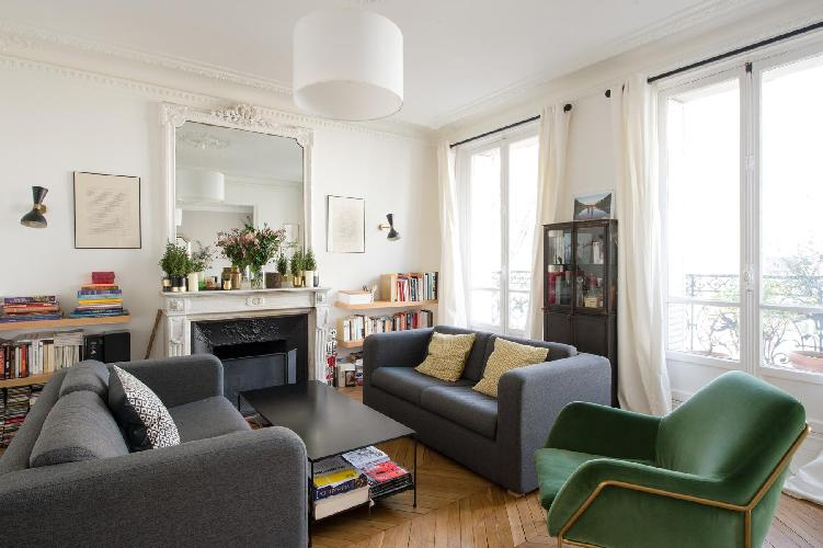 elegant living room with dark-grey sofas, green armchair, some selection of books, white draped wind