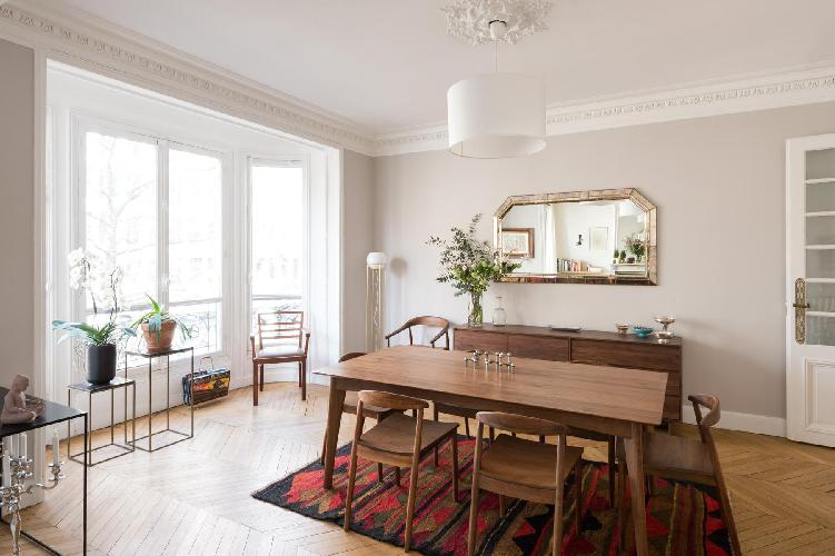 elegant dining room with charming artworks and wooden table and 6 seats in a Paris luxury apartment