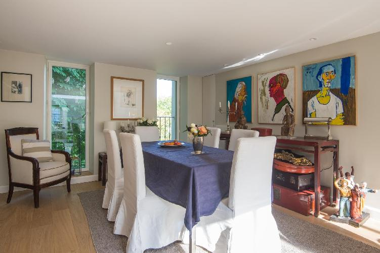 open-plan dining area with antique pieces and framed painting artworks in Paris luxury apartment