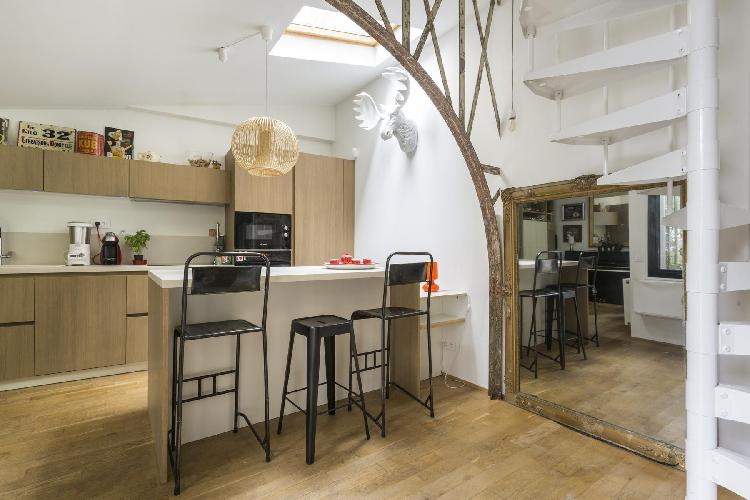 well-equipped kitchen with a piano, breakfast bar and a moose head hang on its white wall in Paris l