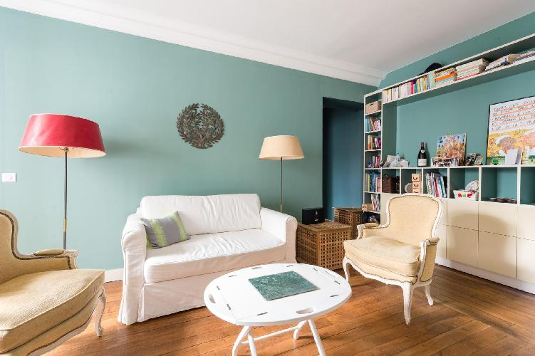 cozy living room in teal, cream, and white hues in Paris luxury apartment