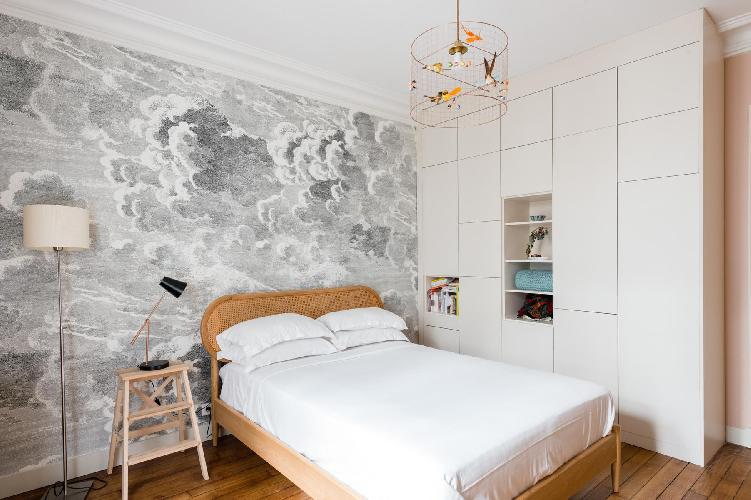 pretty and poised master bedroom painted pale pink, but for one cloud-patterned wall, with a wicker-
