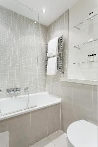 neat and trim bathroom with tub in London Colville Road III luxury apartment