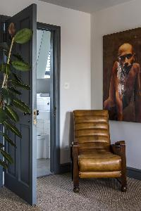 thought-provoking wall art above a lush armchair in London Albion Road luxury apartment