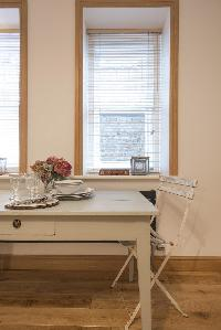 wooden dining table by a tall window in London Addison Bridge Place luxury apartment