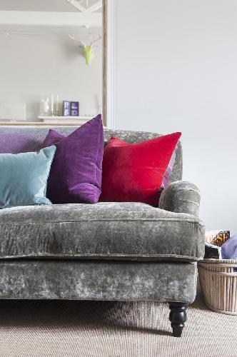 delightful sofa with bright-colored throw pillows in London Cranley Place III luxury apartment