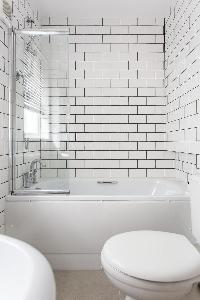 revitalizing white-tiled bathroom with tub in London Beaufort Gardens luxury apartment