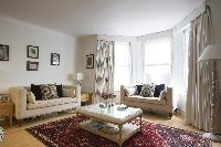 elegant sitting-room sofas by the bay window in London Beaufort Gardens luxury apartment