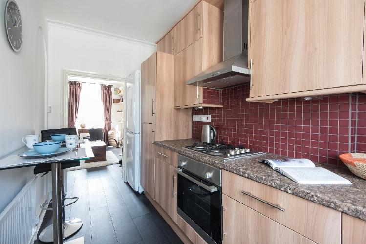 inspiring maroon backsplash in the kitchen of London Coram's Fields luxury apartment