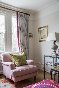 a plush lounge chair by a window in London Albert Bridge Road II luxury apartment