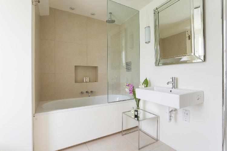 cool bathroom with tub and rain shower in London St Mark's Road IV luxury apartment