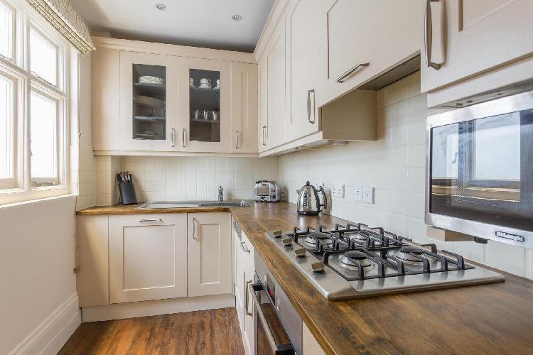 quaint wood-trimmed kitchen with modern appliances in London Cornwall Gardens XX luxury apartment