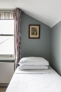 crisp and clean bedroom linens in London Mayfield Avenue II luxury apartment