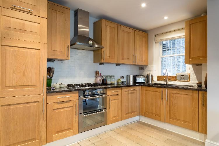beautiful wood-trimmed kitchen cabinets and flooring of London Christchurch Avenue III luxury apartm