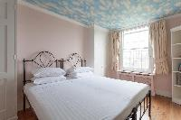 pretty bedroom with wide windows of luxury apartment in Abbey Gardens St John's Wood London