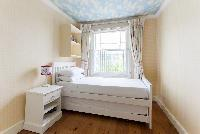 snug bedroom with wide windows of luxury apartment in Abbey Gardens St John's Wood London