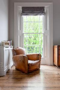 plush lazy chair with distressed-leather look by the tall sitting-room window of luxury apartment in