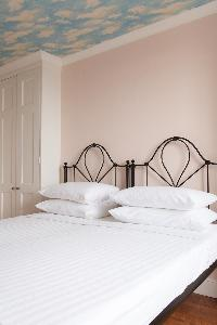 bedroom with muted-pink walls of luxury apartment in Abbey Gardens St John's Wood London