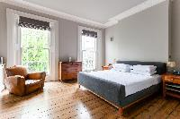 cozy bedroom with tall windows of luxury apartment in Abbey Gardens St John's Wood London