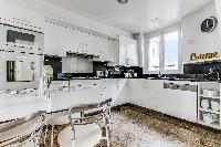 fully equipped white kitchen and mini dining area in a 1-bedroom Paris luxury apartment
