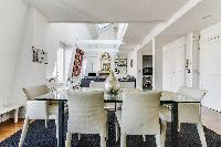 elegant dining area with a large glass table and six seats in a 1-bedroom Paris luxury apartment