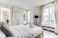 lovely bedroom with a queen-size bed and built-in closet  in a 1-bedroom Paris luxury apartment