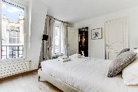 lovely bedroom with a queen-size bed, built-in closet, a desk and a pullout bed in a Paris luxury ap