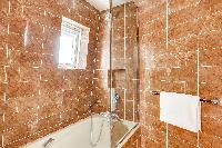 elegant brown-tiled en suite bathroom with a toilet, a sink with mirror, and full bath with shower i