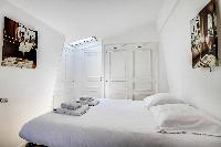 lovely bedroom with a queen-size bed, built-in closet, and skylight in a Paris luxury apartment