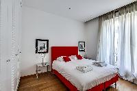 cozy bedroom with a queen-size bed, two-bed side tables, and built-in cabinets  in paris luxury apar