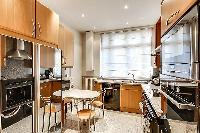well-equipped kitchen with breakfast table in paris luxury apartment