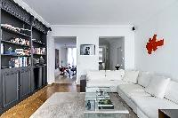 well-lit and spacious living area with two white sofas, black built-in bookshelf filled with books,