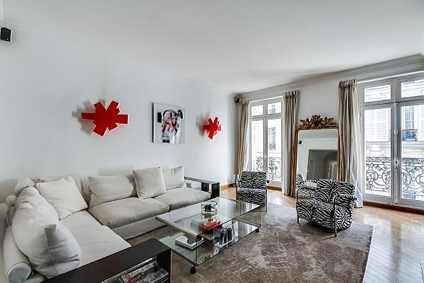 well-lit and spacious living area with two white sofas, big mirror,  grey carpet rug, and tall Frenc