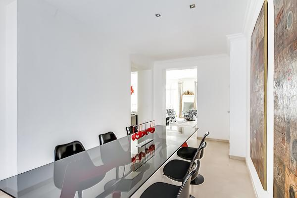 elegant dining area with a long dining table and six chairs in paris luxury apartment