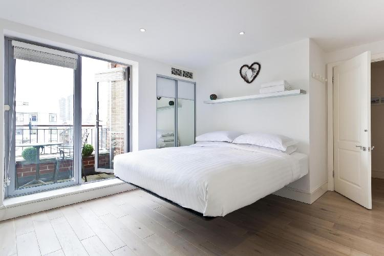 beautiful bedroom with balcony at London Hatton Garden luxury apartment