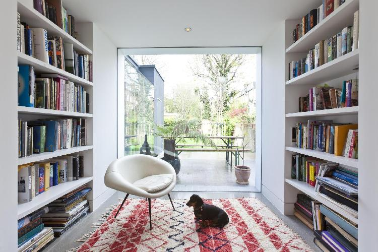 twin shelves filled with books in the glass-walled library of London Brondesbury Road luxury apartme