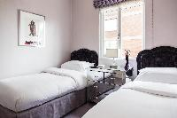twin beds in a room at London Albert Terrace luxury apartment